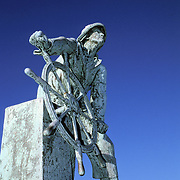"""Fishermen's Memorial Statue (1925).The inscription is taken from Psalm 107, verse 23, line 24, which reads as follows:..""""They that go down to the sea in ships,.That do business in great waters;.These see the works of the Lord,.And his wonders in the deep.""""..The sculptor was Leonard Craske and the dedication was August 23, 1925. The bronze monument consists of a nearly square base of sea green granite, carried from the famous """"Blood Ledge"""" in the Bay View section of Gloucester. The stone is cut with a rough finish to typify the rugged character of the figure, with a single panel on the front holding the bronze letters of inscription, """"They that go down to the sea in ships"""". 1623 - 1923...The pose chosen is that of a helmsman bringing his craft up as close hauled to the wind as possible to clear some dangerous rocks, his eyes being fixed on the sails to detect the first indication that they are beginning to spill the wind, every muscle being strained to hold the wheel firmly until the peril is passed...This is a memorial to all of the Gloucester fishermen who in years since Gloucester was settled in 1623 have lost their lives while fishing. It faces the outer harbor in Gloucester, Massachusetts."""