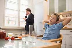 Bored boy in kitchen with father on the phone in background