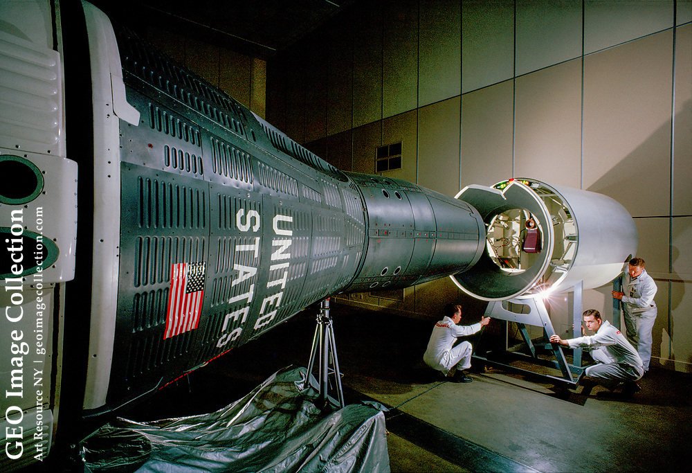 Technicians prepare to connect a housing over the nose of a Gemini capsule.