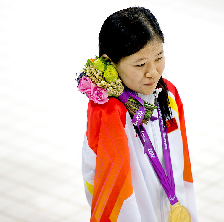 Engeland, Londen, 30-08-2012.<br /> Paralympische Spelen.<br /> Zwemmen, Vrouwen, 100 meter rugslag S6, Finale.<br /> Dong Lu uit China heeft het goud gewonnen in een nieuw wereldrecord van 1.24.71 en loopt na de huldigingsceremonie weg met de gouden medaille en het bosje bloemen tussen hoofd en schouder geklemd omdat zij geen armen heeft.<br /> Foto : Klaas Jan van der Weij
