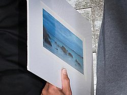 © Licensed to London News Pictures. 22/09/2016. London, UK. C J De Mooi, real name Joseph Connagh, carries a photograph or painting of the sea as he is released on bail from Westminster Magistrates Court in London where he faces extradition to Holland. Former panellist on the BBC quiz show Eggheads, who admitted in his autobiography to possibly killing someone while in Holland, was arrested on a European arrest warrant at Heathrow airport. Photo credit: Peter Macdiarmid/LNP