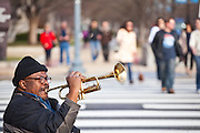 An African-American man plays jazz trumpet on a crowded street pedestrian crossing in downtown Washington DC.
