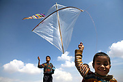 Ehsan, 13, the eldest son of Noor Agha, at left, and Saboor, 6, at right, fly the kites next to his house inside the cemetery, Kabul, Afghanistan, Saturday, March, 10, 2007. Noor Agha is a renowned kite maker who made kites for the movie makers of the best-selling novel, The Kite Runner, which will be distributed by Dreamworks and Paramount Vantage in Nov. this year. Noor Agha's wives, using their special glue, help him produce enough kites to please the clients' needs. Some of his children can also make their own kites with plastic bags and bamboo sticks. As the Afghan New Year's Day (Nawruz) approaching on March 21, the finger tips of Noor Agha's family got busier for mass production.