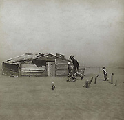 Storm in the Dust Bowl, America, 1930s.  Man and boys walking towards wooden hut gradually being covered by wind-blown dust. Small boy is holding up his hand to protect his face.