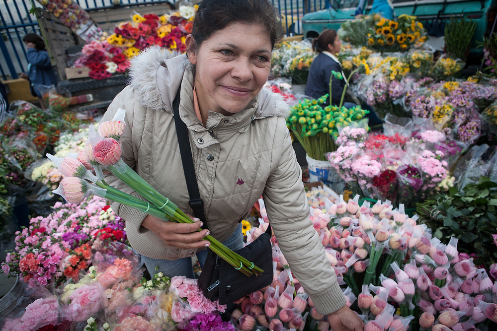 A woman sells flowers in the Palo Quemado market in Bogota