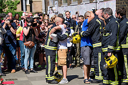 19/06/2017. London, UK. Family of fire victim Jessica Urbano are joined by firefighters who attended the scene, at a minutes silence held near the scene of the Grenfell tower block fire. The blaze engulfed the 27-storey building killing dozens - with 34 people still in hospital, many of whom are in critical condition. Photo credit: Ben Cawthra *** Please Use Credit from Credit Field ***