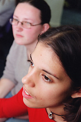 Close up of teenage girl with physical disability using computer with friend in college library,