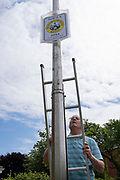 A local elderly man descends his ladder after fixing into place, a Neighbourhood Watch sign on a lamp post, on 30th May 2021, in Nailsea, North Somerset, England.