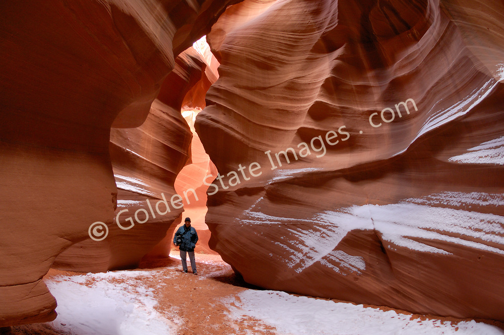 Hiker enters Slot Canyon.<br /> <br /> Antelope Canyon is located on LeChee Navajo lands near Page Arizona.  The area is managed by the Navajo Tribe.  <br /> Sandstone slot canyons are formed over centuries by the scouring action of water from storm runoff and wind. <br /> Depending on the time of day the curving walls glow in shades of red orange and yellow.   <br /> <br /> Upper Antelope Canyon is also known as The Corkscrew.