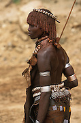 A Hamar female dancer at a bull jump, a ritual at which a young man runs across the backs of a number of bullocks in order to become eligible for marriage, in South Omo, Ethiopia. The antelope skin and metal necklace indicate that she is married, while her belt studded with cowry shells shows she is a mother. Her hair and neck are coated in butter and red ochre and she has scarifications on her arms and shoulders. The 40,000-strong, cattle-herding Hamar are among the largest of the 20 or so ethnic groups which inhabit the culturally diverse Omo region in south-west Ethiopia.