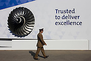 A British military officer walks past the Rolls-Royce corporate chalet at the Farnborough Air Show, England. The corporate message promising a trusted deliverence of excellence is read by the man as he passes the model of the aerospace company's jet engine.