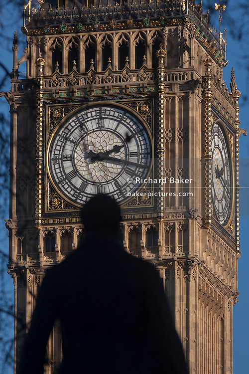 """The silhouetted statue of Sir Robert Peel and the clockface containing the Big Ben bell in the Elizabeth Tower of the British parliament, on 17th January 2017, in London England. The Elizabeth Tower (previously called the Clock Tower) named in tribute to Queen Elizabeth II in her Diamond Jubilee year – was raised as a part of Charles Barry's design for a new palace, after the old Palace of Westminster was largely destroyed by fire on the night of 16 October 1834. The new Parliament was built in a Neo-gothic style, completed in 1858 and is one of the most prominent symbols of both London and England. Sir Robert Peel, was a British statesman and member of the Conservative Party, served twice as Prime Minister of the United Kingdom and twice as Home Secretary. He created the modern police force and officers known as """"bobbies"""" and """"peelers"""""""