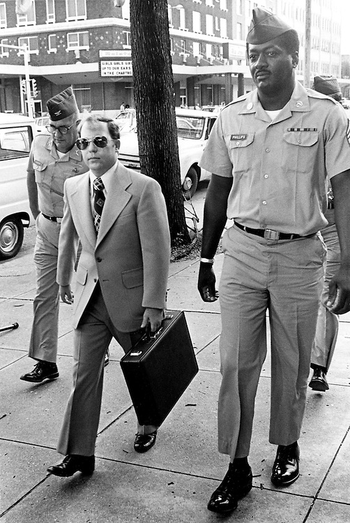 """Convicted of the murder of 102 VietNamese civilians  -the My Lai Massacre - former U.S. Army Lieutenant William Calley (sunglasses) is escorted from the Fort Benning, Georgia confinement facility to a federal appeals court in nearby Columbus, Ga. At a later date, Calley's original sentence of life in prison was turned into an order of house arrest, but after three years, President Richard Nixon reduced his sentence with a presidential pardon -- Determine pricing and license this image, simply by clicking """"Add To Cart"""" below --"""
