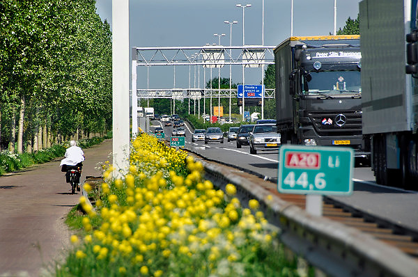 Nederland, Gouda, 7-5-2008..Verkeersdrukte op de A20. Een vrouw fietst op een smalle weg naast de snelweg...Foro: Flip Franssen/Hollandse Hoogte