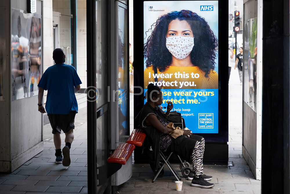 HM Government, Public Health England, NHS advertising boards advise people to take precaution of wearing a face mask as some non-essential shops re-open, shoppers return to Oxford Street while social distancing measures are put in place by the various retail shops which are open on 26th June 2020 in London, England, United Kingdom. As the July deadline approaces and government will relax its lockdown rules further, the West End remains quiet, apart from this popular shopping district, which itself has far fewer people on its pavements than normal.