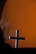 Lonely Cross in silhouette against orange sky   Ensomt kors i silhuett mot orange himmel.