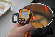 Handheld laser remote thermometer measures the temperature of boiling oil 144 degrees Celsius