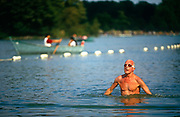 A male swimmer stands up after doing the Crawl across this scene of fresh water bathing in the Serpentine Lake in London's Hyde Park. This bathing area is where the normally busy Serpentine Swimming Club has the use of this Royal Lake known as Lansbury's Lido. It is now normally open only in the summer, but one traditional event occurs each year on New Year's Day, when the ice is broken and brave bathers dive into the cold waters of the lake. The Serpentine will be used for the swimming leg of the triathlon at the London 2012 Olympics. The pool was formed in 1730, its name from a snakelike, curve. Queen Caroline wife of George II ordered the damming of the River Westbourne and other natural ponds in Hyde Park.