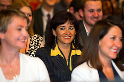 © Licensed to London News Pictures. 12/09/2015. London, UK. LAURA ALVEREZ, wife of Jeremy Corbyn, sat behind YVETTE COOPER (left) and LIZ KENDALL (right), smiling at the announcement of Jeremy Corbyn as the new Labour Party leader. The announcement of the new leader of the Labour Party at the QEII centre in Westminster, London on September 12, 2015. Former leader ED Miliband resigned after a heavy defeat at the last election. Photo credit: Ben Cawthra/LNP