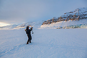 Glaciologist Poul Christoffersen takes pictures from the sea ice in Templefjorden of the tidewater terminus of Tunabreen, Svalbard. Ultunafjella (right) and Gerardfjella are visible across the fjord.