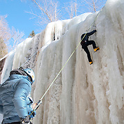 """Dan Hawes of Hanson, Massachusetts, climbs the frozen Champney Falls in the White Mountain National Forest. He uses 12 pointed crampons mounted on insulated plastic mountaineering boots, and an ice axe in each hand to aid her ascent of the waterfall. A rope attached to his climbing harness runs to an anchor at the top of the route, then down to his climbing partner and wife Jen Hawes, who ensures that he is """"on belay' in case of a slip or fall."""