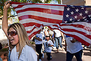 Apr. 19, 2009 -- PHOENIX, AZ: A woman carries an American flag during a march through central Phoenix Sunday. About 2,000 people marched from the Arizona State Capitol to Cesar Chavez Plaza in downtown Phoenix. The march was organized by the United Farm Workers of America to promote immigration reform.  Photo by Jack Kurtz