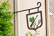 A wrought iron painted sign that illustrates the theme of champagne and wine production: a vine leaf vines and a cutting knife to do pruning, the village of Hautvillers in Vallee de la Marne, Champagne, Marne, Ardennes, France
