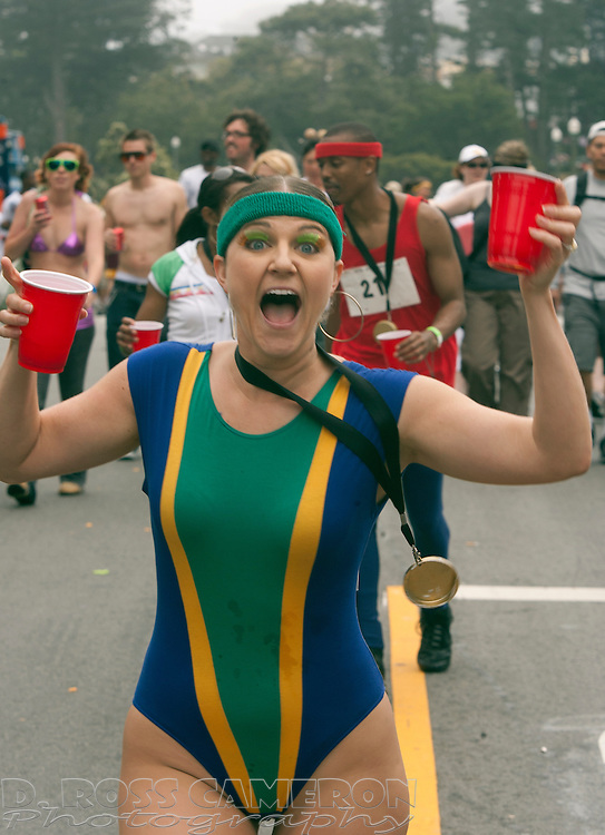 """An unidentified woman wearing a swimsuit and a """"gold medal"""" runs through Golden Gate Park at the 97th running of the Bay to Breakers 12K race, Sunday, May 18, 2008 in San Francisco. (Photo by D. Ross Cameron)"""