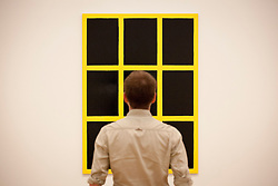© Licensed to London News Pictures. 03/06/2013. London, UK. A Tate Britain employee views 'Yellow Window' (2002) a painting by British artist Gary Hume at the press view for an exhibition of his work at the Tate Britain in London today (03/06/2013). The exhibition, running in tandem with an exhibition by British artist Patrick Caulfield, is open to the public from 5th June - 1st September 2013 at the Tate Britain. Photo credit: Matt Cetti-Roberts/LNP