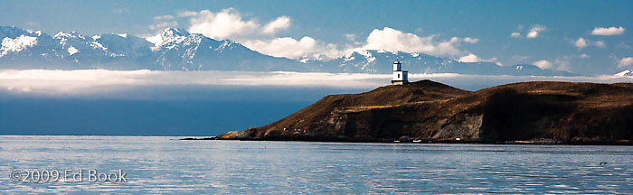 Cattle Point Lighthouse on San Juan Island with the Olympic Mountains in the distance, Washington, USA