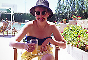 Close up portrait os smiling woman holding a drink by swimming pool on Mediterranean  holiday 1966