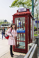 Shanghai, China - April 7, 2013: one stylish young chinese woman smiling in a street at the city of Shanghai in China on april 7th, 2013