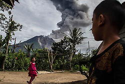 May 20, 2017 - Karo, North Sumatra, Indonesia - A childs playing in their home on bursts of thick volcanic ash volcano Sinabung volcano into the air, in Karo on May 19, 2017, North Sumatra Province, Indonesia.  People are urged to remain vigilant and adhere to government recommendations. It is unpredictable how long Mount Sinabung will stop erupting. Volcanic parameters and mountain seismicity remain high so that the potential for further eruptions will continue. (Credit Image: © Ivan Damanik via ZUMA Wire)