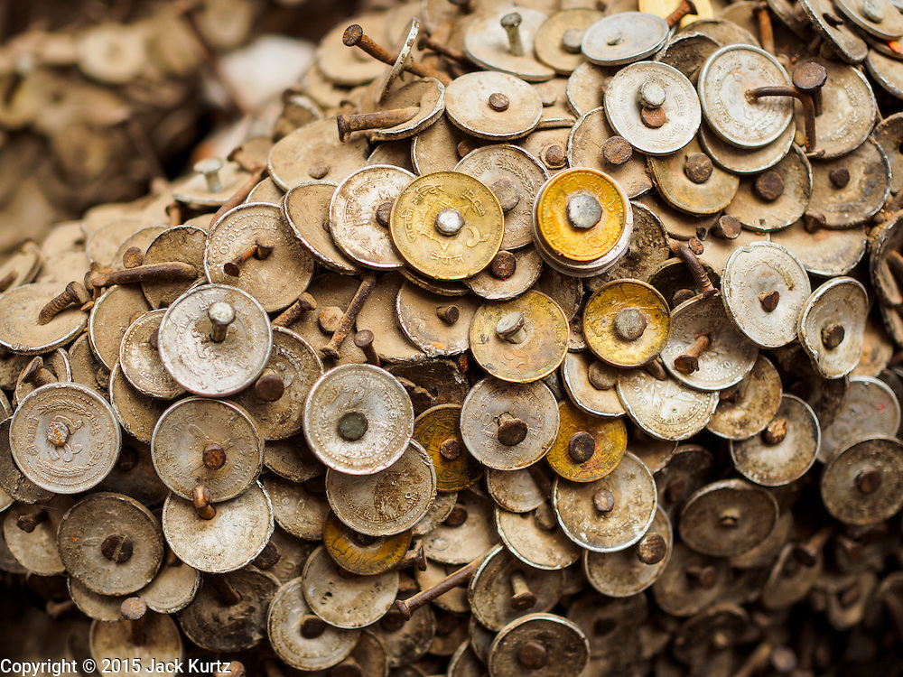 01 AUGUST 2015 - KATHMANDU, NEPAL:  Coins pounded into a piece of wood in Kathmandu. Nepalese believe the wood is connected to dentistry and pound nails into the wood when they have toothaches.     PHOTO BY JACK KURTZ