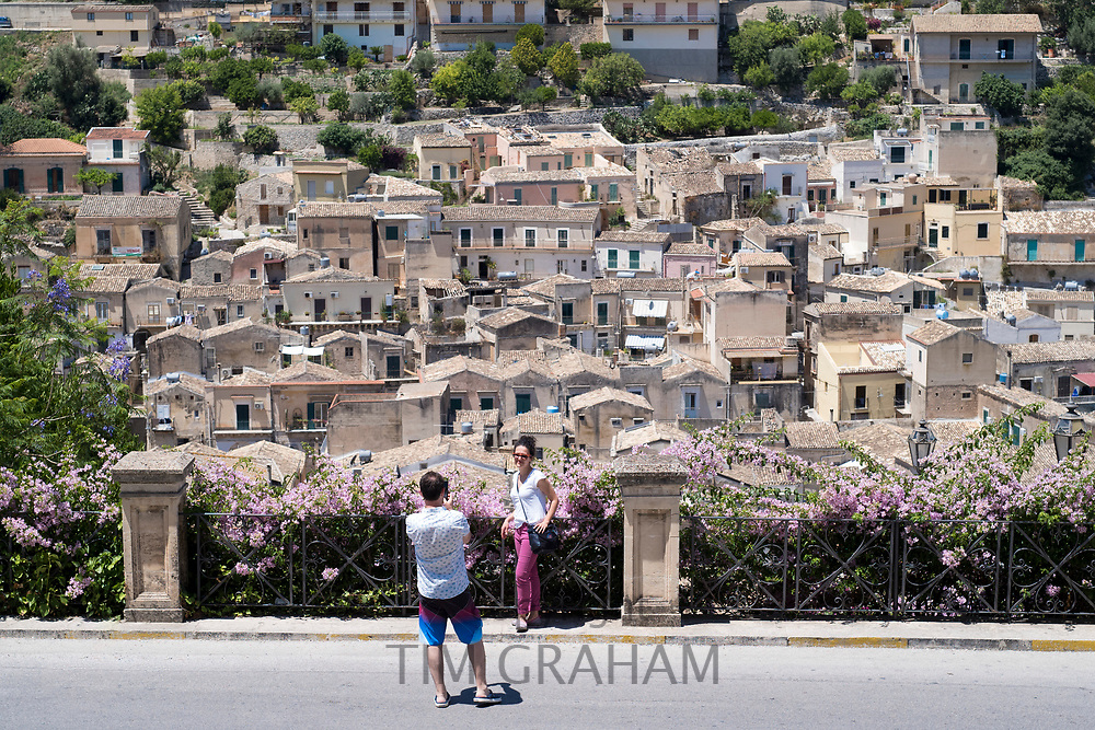 Tourists taking souvenir photographs on a smartphone in Modica Alta with view of Modica Bassa and Baroque architecture, Sicily