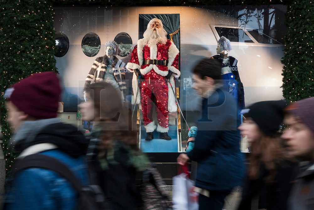 © Licensed to London News Pictures. 23/12/2016. London, UK. A Santa Clause mannequin looks down on shoppers from a Selfridges window in Oxford Street on the last working day before Christmas. Photo credit: Peter Macdiarmid/LNP