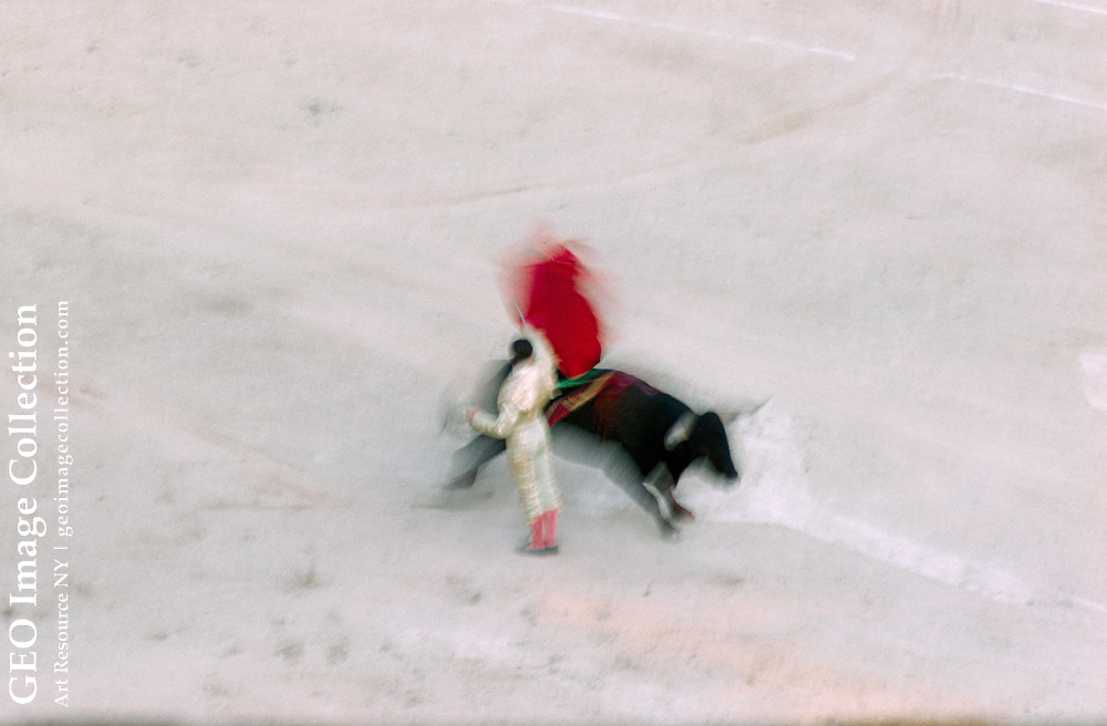 Blurred motion shot of a bull and a matador in a bull fighting ring.