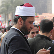 A sheikh checks his mobile phone during the Day of Justice and Cleansing in Cairo's Tahrir Square.