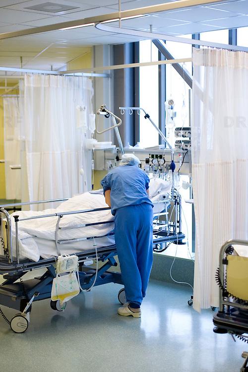 Nederland Rotterdam  25-08-2009 20090825 Foto: David Rozing .Serie over zorgsector, Ikazia Ziekenhuis Rotterdam. ..Foto: David Rozing Serie over zorgsector, Ikazia Ziekenhuis Rotterdam. Een verpleegkundige controleert een patient op de recoveryroom, dit is een zaal waar patienten na een operatie verzorgd worden. Patient is being checked by doctor, in recovery room, where people are looked after, after surgery. ziekenzaal, op zaal liggen Holland, The Netherlands, dutch, Pays Bas, Europe, professionele, professional, steriel, steriele omgeving, werkkleding, kledingvoorschriften, , genezen, genezing, ziekte bestrijding bestrijden, ernstig ziek zijn, ..Foto: David Rozing..Holland, The Netherlands, dutch, Pays Bas, Europe, ronde doen, routine verpleegkundigen, op zaal liggen, behandelplan, treatment,.,ziektekosten,zorgverlener, zorgverleners,zorgverlening, overzicht, general view,verpleger, verplegers, verplegend, status
