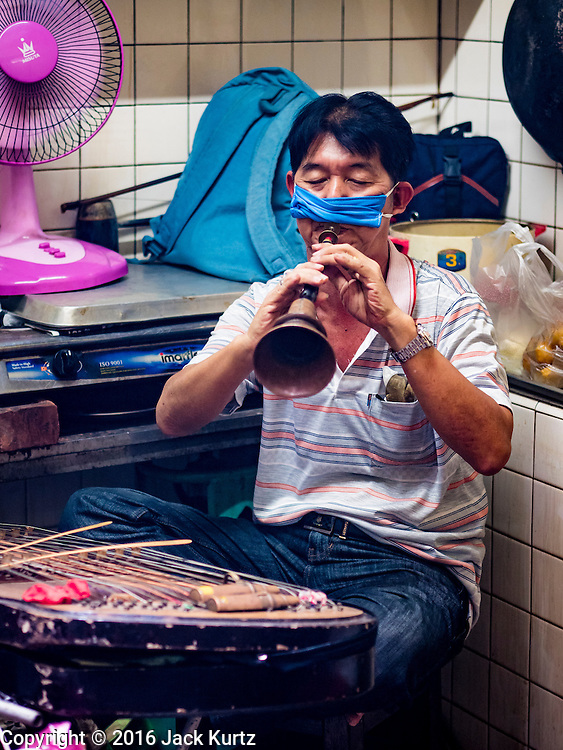 16 SEPTEMBER 2016 - BANGKOK, THAILAND: A traditional musician performs in a back room at Heng Chia Shrine on Chareon Krung Road during the Mid-Autumn Festival in Bangkok. The festival was originally a time to enjoy the successful reaping of rice and wheat and is still celebrated as a harvest festival in agricultural communities. In Bangkok, people make food offerings in honor of the moon. And it is an opportunity to share mooncakes.   PHOTO BY JACK KURTZ