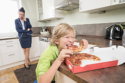 Boy eating pizza while mother has business call in kitchen, Bavaria, Germany