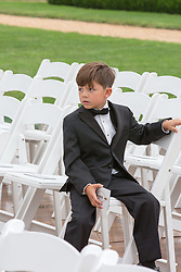 little boy at a wedding seated outdoors