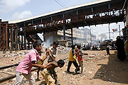 Children are playing inside the slum next to the train station of Bandra (East), Mumbai, India, where famous child actors Azharuddin Ismail and Rubina Ali, playing the roles of 'young Salim' and 'young Latika' in the movie Slumdog Millionaire, winner of 8 Oscar Academy Awards in December 2008, still live with their families. Various promises were made to lift the two young actors from poverty and slum-life but as of the end of May 2009 anything is yet to happen. Rubina's house was recently demolished with no notice as it lay on land owned by the Maharashtra train authorities and she is now permanently living with her uncle's family in a home a stone-throw away in the same slum. Azharuddin's home too was demolished in the past two weeks, as it happens every year in his case, because the concrete walls were preventing local authorities to clear a drain passing right behind it. As usual, his father is looking into restoring the walls as soon as the work on the drain has been completed.