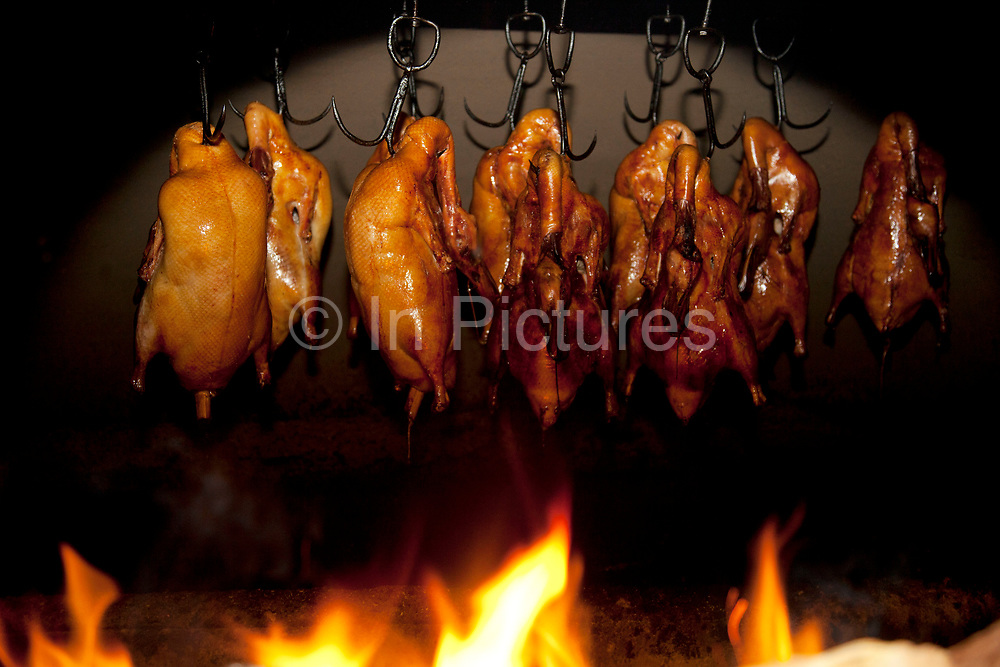 Behind the scenes in the kitchen where the ducks are roasted in wood burning ovens. Quanjude roast duck restaurant in Wangfujing, Beijing. This is a Chinese restaurant known for its trademark Peking Roast Duck and is known for being the best roast duck restaurant in China. Quanjude was established in 1864 during the Qing Dynasty under the reign of the Tongzhi Emperor. Although Peking Duck can trace its history many centuries back, Quanjude's heritage of roast duck preparation - using open ovens and non-smoky hardwood fuel such as Chinese date, peach, or pear to add a subtle fruity flavor with a golden crisp to the skin, was originally reserved for the imperial families.