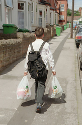 Young boy returning home from school carrying school bag and shopping bags,