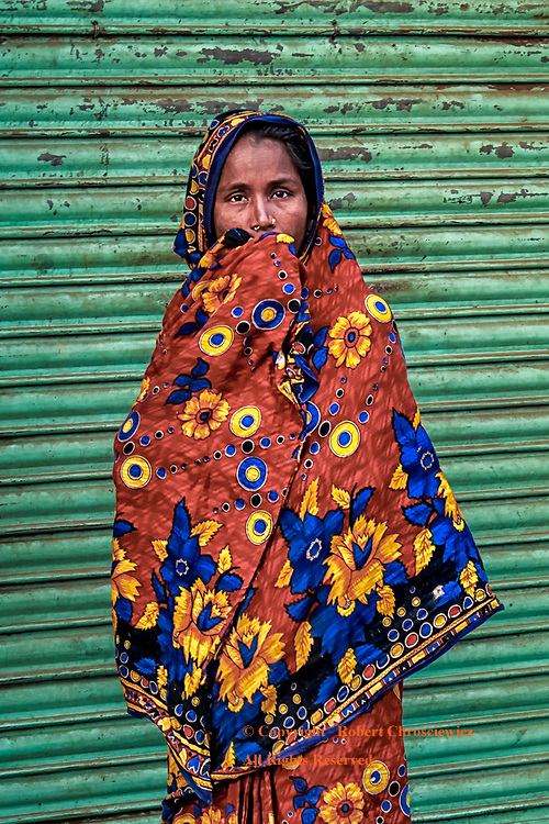 Fashionably Shy: A woman caught alone on the street, hides behind her fabulously colourful saree, Dhaka Bangladesh.