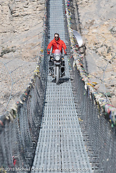 Sean Lichter riding across a narrow suspension bridge over the Kali Gandaki River on day-6 of our Himalayan Heroes adventure riding from Muktinath to Tatopani, Nepal. Sunday, November 11, 2018. Photography ©2018 Michael Lichter.
