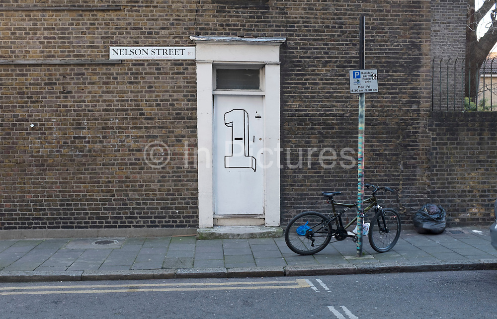 Number 1 Nelson Street, London. Large figure one painted onto the door of this terraced end house.