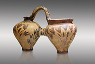 Minoan decorated double ewer with crocus flower  design,  Poros Heraklion 1800-1650 BC;  Heraklion Archaeological  Museum, grey background. .<br /> <br /> If you prefer to buy from our ALAMY PHOTO LIBRARY  Collection visit : https://www.alamy.com/portfolio/paul-williams-funkystock/minoan-art-artefacts.html . Type -   Heraklion   - into the LOWER SEARCH WITHIN GALLERY box. Refine search by adding background colour, place, museum etc<br /> <br /> Visit our MINOAN ART PHOTO COLLECTIONS for more photos to download  as wall art prints https://funkystock.photoshelter.com/gallery-collection/Ancient-Minoans-Art-Artefacts-Antiquities-Historic-Places-Pictures-Images-of/C0000ricT2SU_M9w