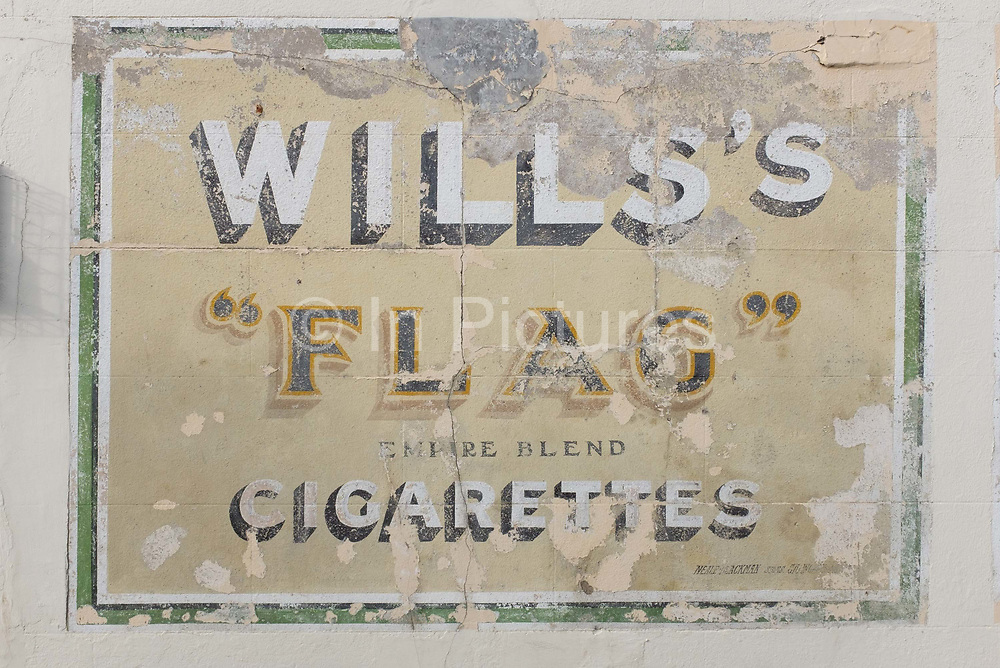 A detail of old advertising for a cigarette brand from decades ago called Wills whose product was Flag Empire Blend, on 19th July 2020, in Whitstable, Kent, England. W.D. & H.O. Wills was a British tobacco importer and manufacturer formed in Bristol, England. W.D. & H.O. Wills was founded in 1786 and was the first UK company to mass-produce cigarettes. It was one of the founding companies of Imperial Tobacco along with John Player & Sons.
